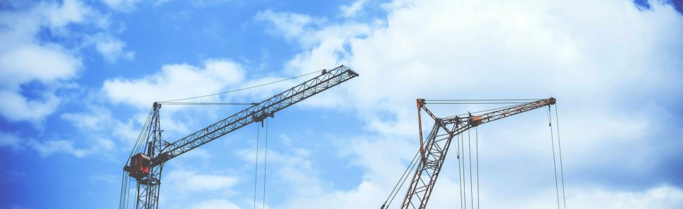2 cranes against backdrop of blue cloudy sky representing growth in construction industry
