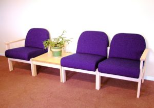 3 purple chairs with beech frames and matching coffee table in reception area