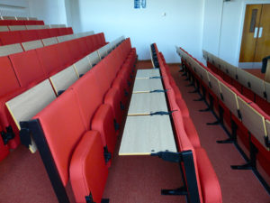 Individual flip-up desks attached to seat backs in a university lecture theatre