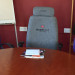 3 seats around a boardroom table with job titles embroidered on seat backs