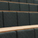 Close up of refurbished lecture theatre seats in dark grey fabric