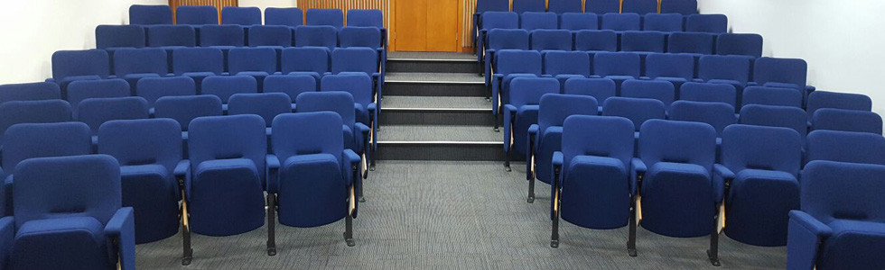 Lecture theatre with Evertaut Aspire Conference Seating upholstered in blue fabric with flip-up writing tablets