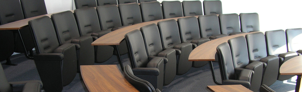 Lecture theatre with Evertaut Aspire Lecture Theatre Seating upholstered in black vinyl with oak effect curved desks