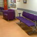 Hospital corridor with Evertaut Dandi beam seating upholstered in purple vinyl