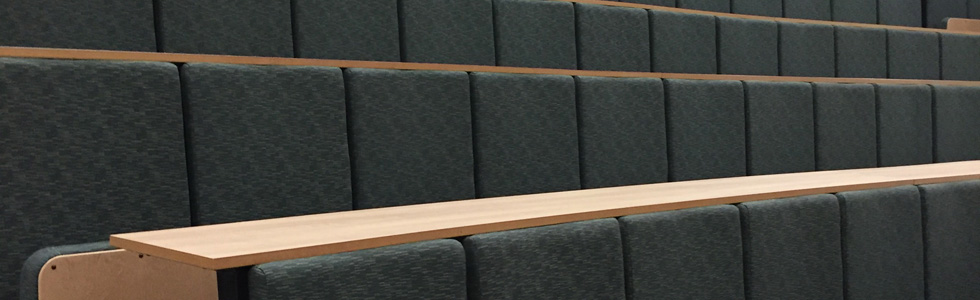 Close up refurbished by Evertaut lecture theatre seats upholstered in grey fabric with laminate writing desks and matching underseat boards