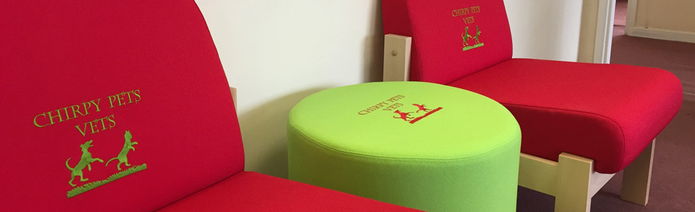 Close up of Evertaut red reception chairs and bright green padded stool embroidered with Chirpy Pets Vets logo
