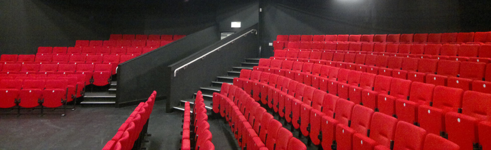 Studio theatre with black walls and floor with Evertaut Solar Theatre Seating upholstered in bright red fabric