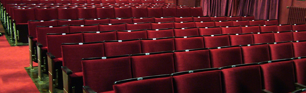 Theatre with traditional theatre seating refurbished by Evertaut with upholstery in deep red velvet fabric and exposed wooden seat backs