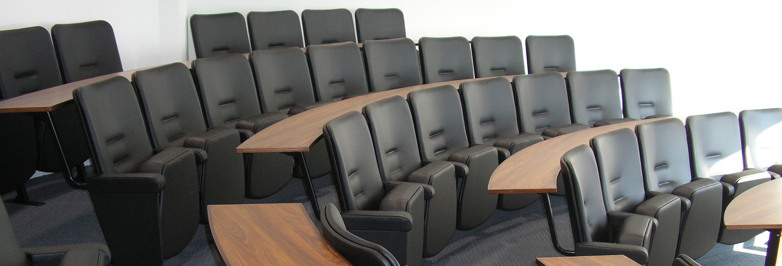 Evertaut Aspire lecture theatre and conference seating upholstered in black vinyl with oak effect desks