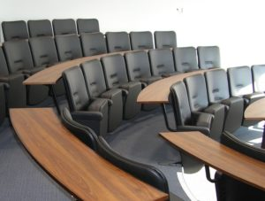 Lecture theatre with black lecture chairs and curved oak effect desks