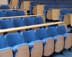 university lecture theatre with blue lecture chairs fitted in angled rows with beech effect desks