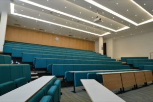 Lecture chairs fitted in angled rows in a university lecture theatre