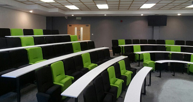 Black and green lecture chairs positioned in curved rows in a lecture theatre