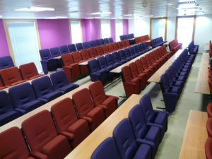 Lecture theatre with red and purple seats and rows of fixed desks