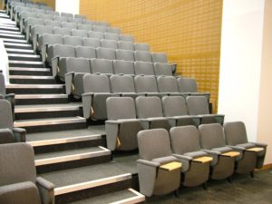 Lecture chairs with folding writing tablets in arm in large lecture theatre