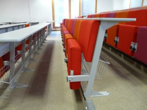 Lecture theatre with storage baskets under desks attached to back of lecture chairs