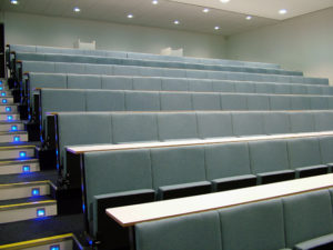 Large lecture theatre with pale blue lecture chairs and blue led lights in stairs