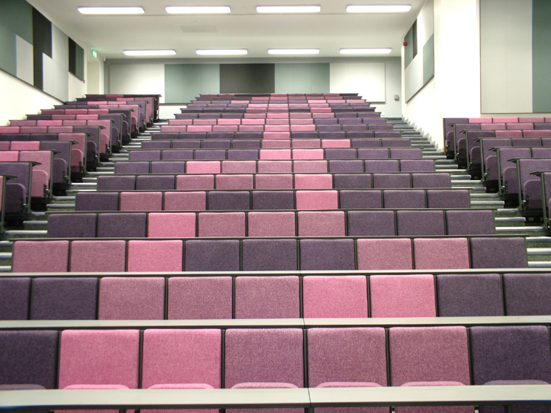 Large tiered lecture theatre with pink and purple lecture chairs