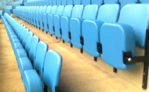 Rows of Sky blue upholstered stadium seats in a football stadium