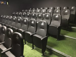 Rows of black upholstered stadium seats on artificial turf within Swansea City FC training facility