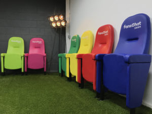 Football themed reception area with stadium seats, artificial turf and floodlight