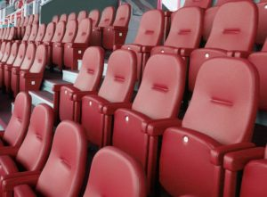 Football stadium with rows of red upholstered stadium seats