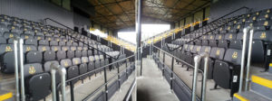 Rows of Club and VIP black upholstered stadium seats with embroidered logos in Southport FC football stadium