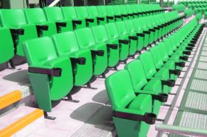 Rows of green upholstered stadium seats with cup holders in a sports stadium