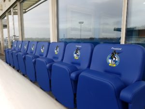 Row of upholstered stadium seats with club logo outside Chairman's suite at Bristol Rovers FC