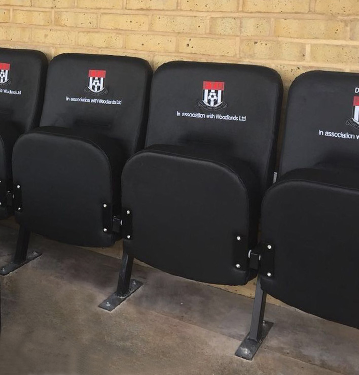Row of black upholstered seats with embroidered club logo in a football stadium