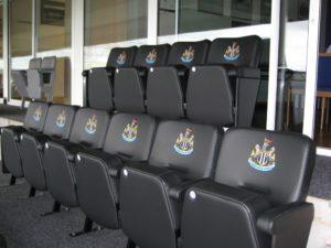Black VIP stadium seats outside an executive box at Newcastle United FC