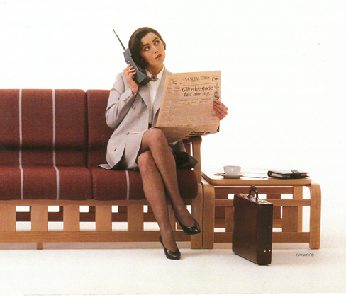 Businesswoman with mobile phone and FT newspaper sat on Evertaut reception seating in early 1990s