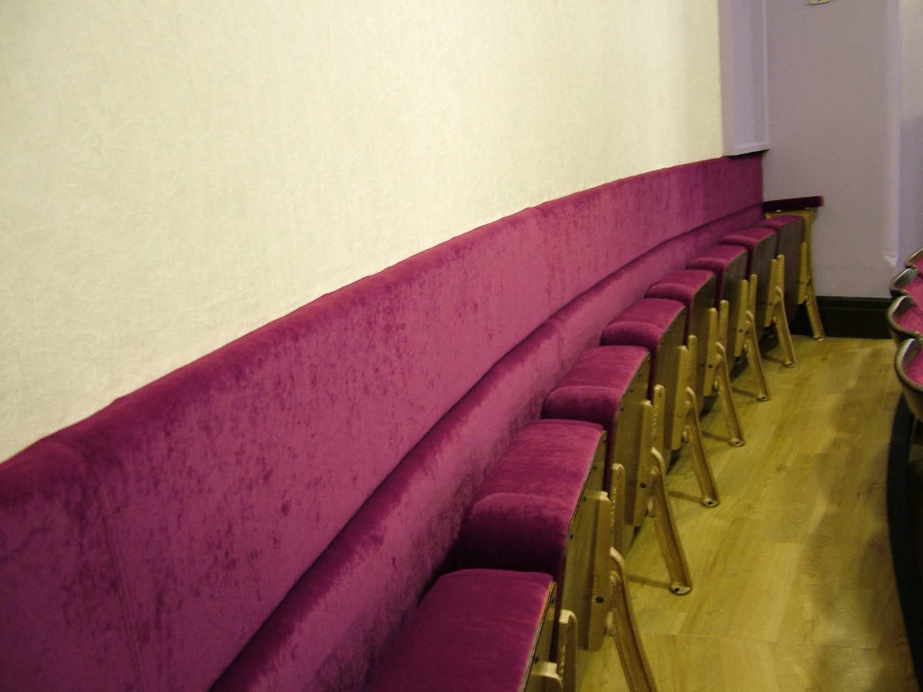 Back row of theatre seating with padded back wall panel upholstered in deep red velvet