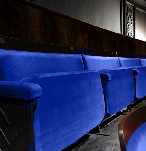 Back row of theatre with double love seats upholstered in blue velvet fabric