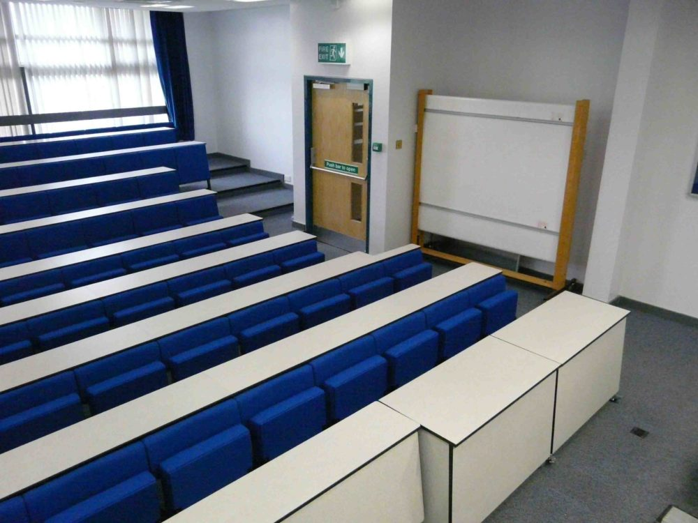Blue lecture chairs and white desks with transportable front row desks in a university lecture theatre