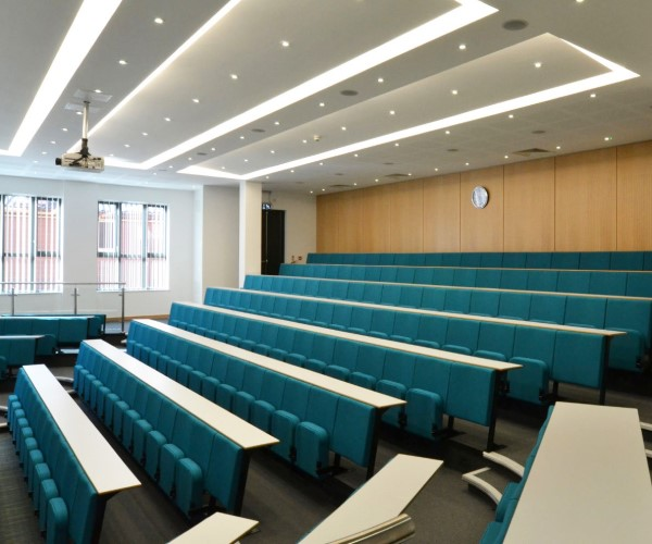 Auditorium style lecture theatre with Evertaut Diploma lecture theatre seating upholstered in green blue fabric