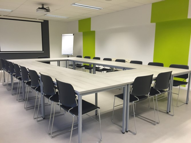 Conference room with chairs positioned around central tables in an oblong shape