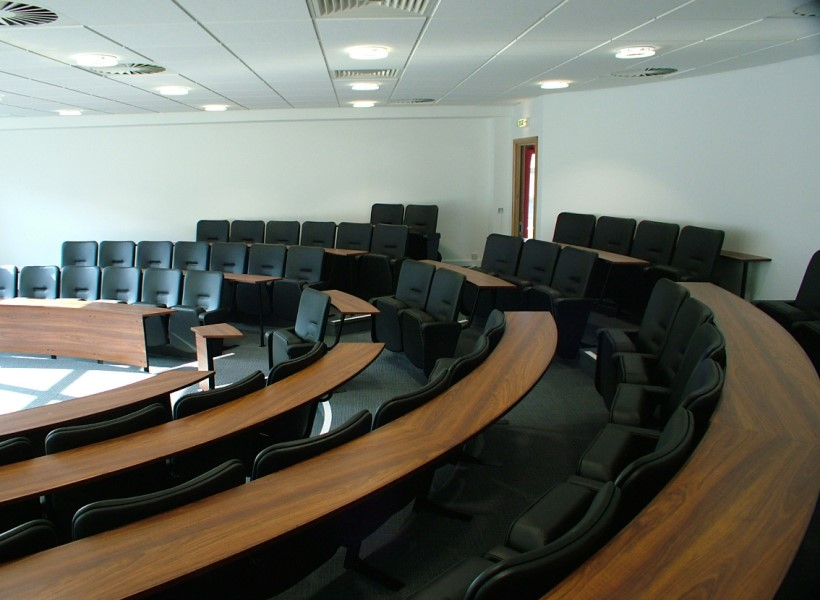 University lecture theatre with black lecture theatre seating fixed in curved rows