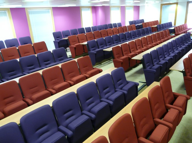 Purple and red lecture theatre seating in straight rows in a university lecture theatre
