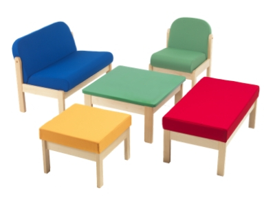 Set of children's waiting room furniture comprising deeply cushioned low chairs and bench seating upholstered in primary colours and a table