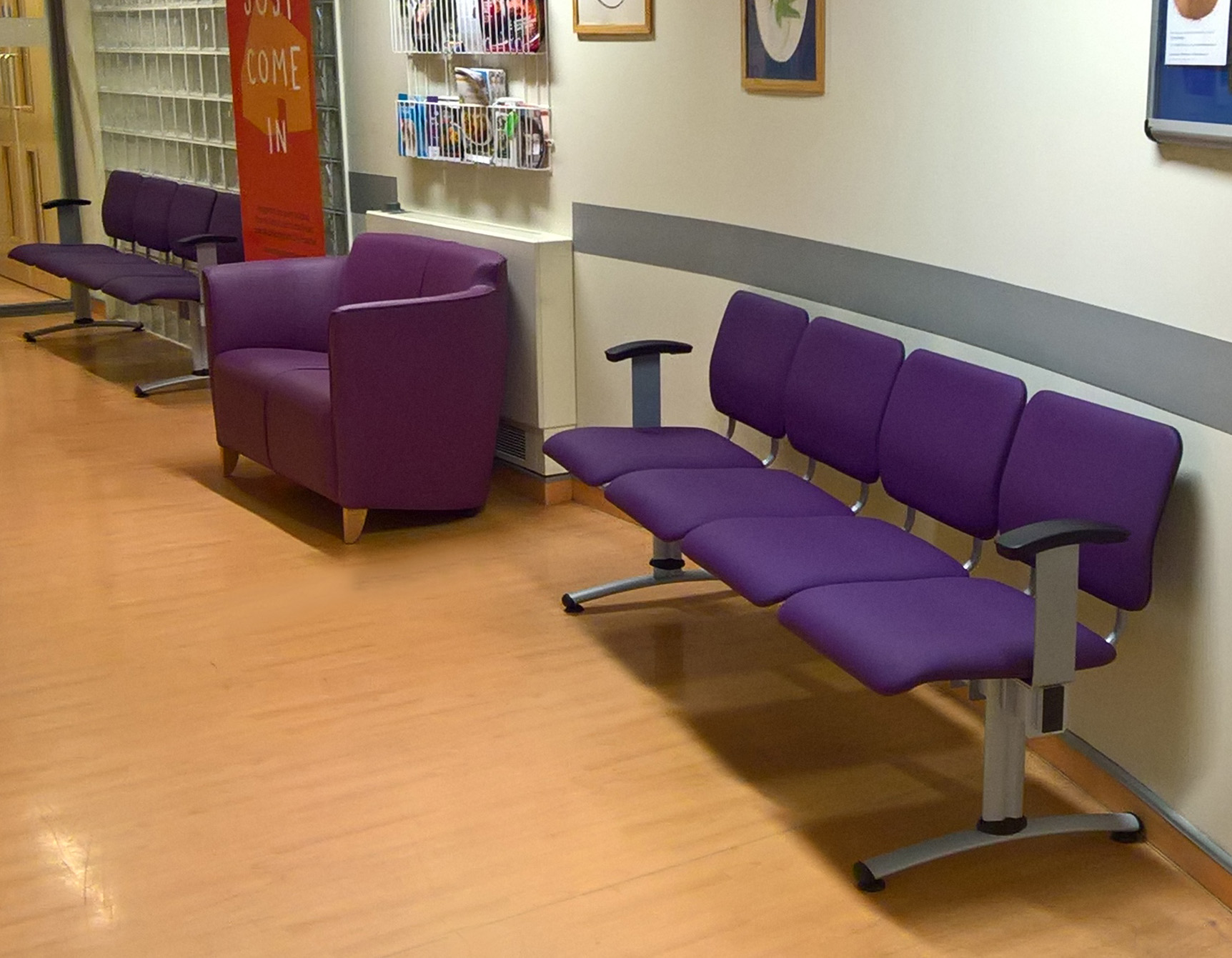 Hospital corridor waiting area with purple 4-seat beam seating and co-ordinating small sofa