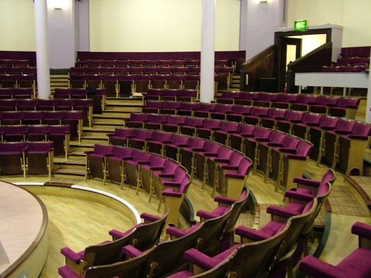 Curved theatre auditorium with purple fixed seating after refurbishment