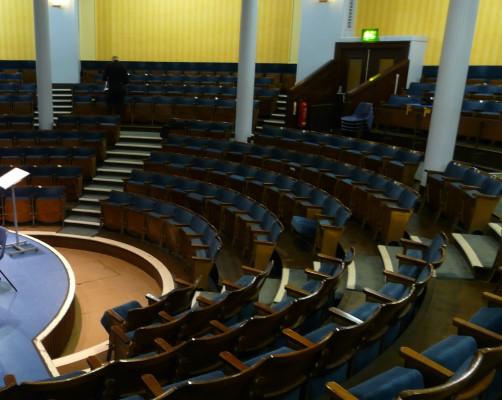 Curved theatre auditorium with blue fixed seating before reupholstery