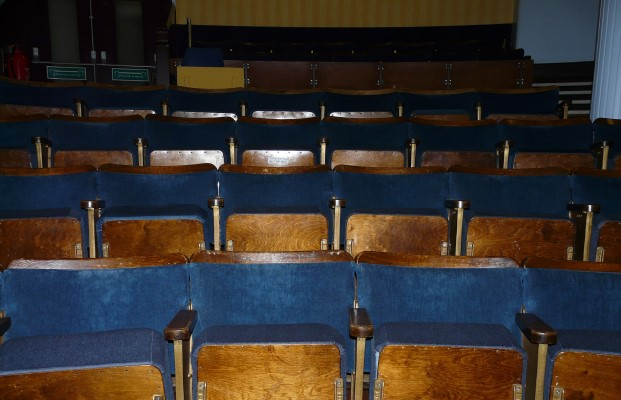 Close up of blue fixed seating in a theatre before refurbishment