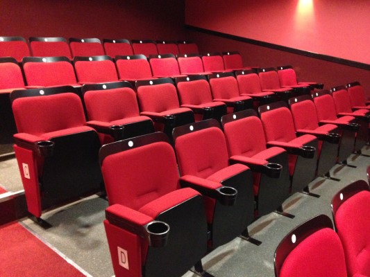 Fixed seating in a small cinema auditorium with wooden back and seat boards
