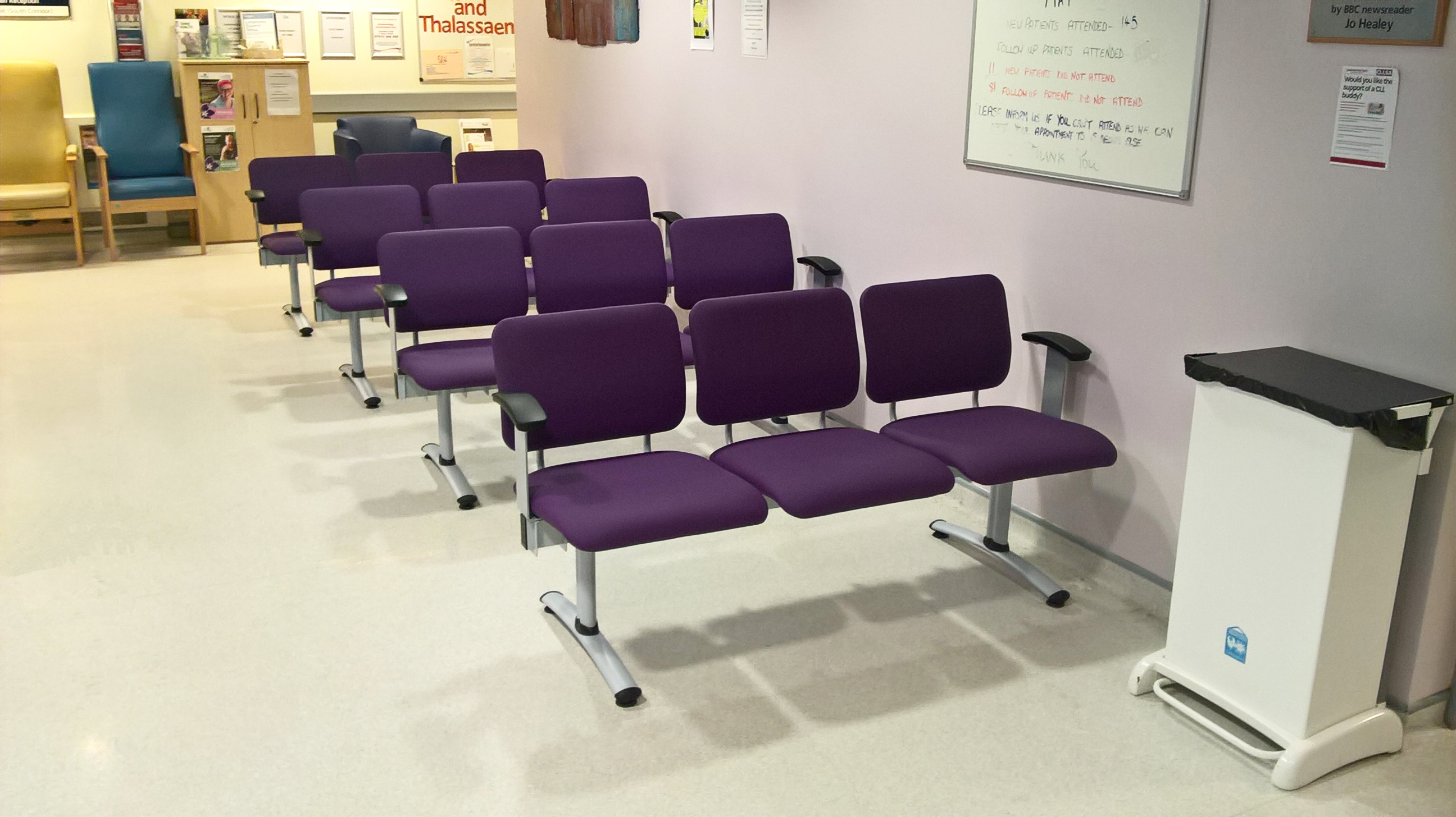Hospital waiting room with rows of 3-seat beam waiting room chairs upholstered in purple vinyl