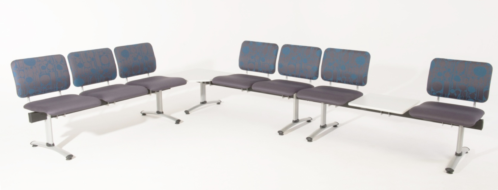 Configuration of beam seating with every 3 seats separated by an integral table including a corner table