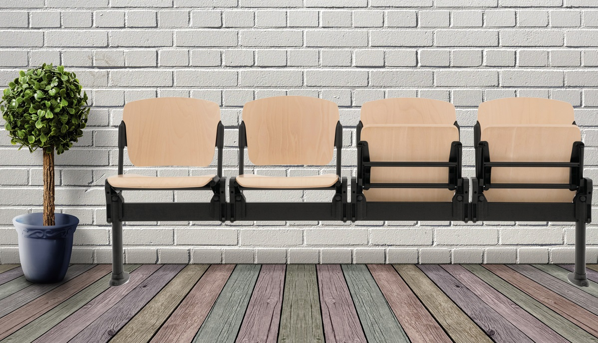 4 wooden seats on a beam on a multi coloured wooden floor with white brick wall background and large plant in pot