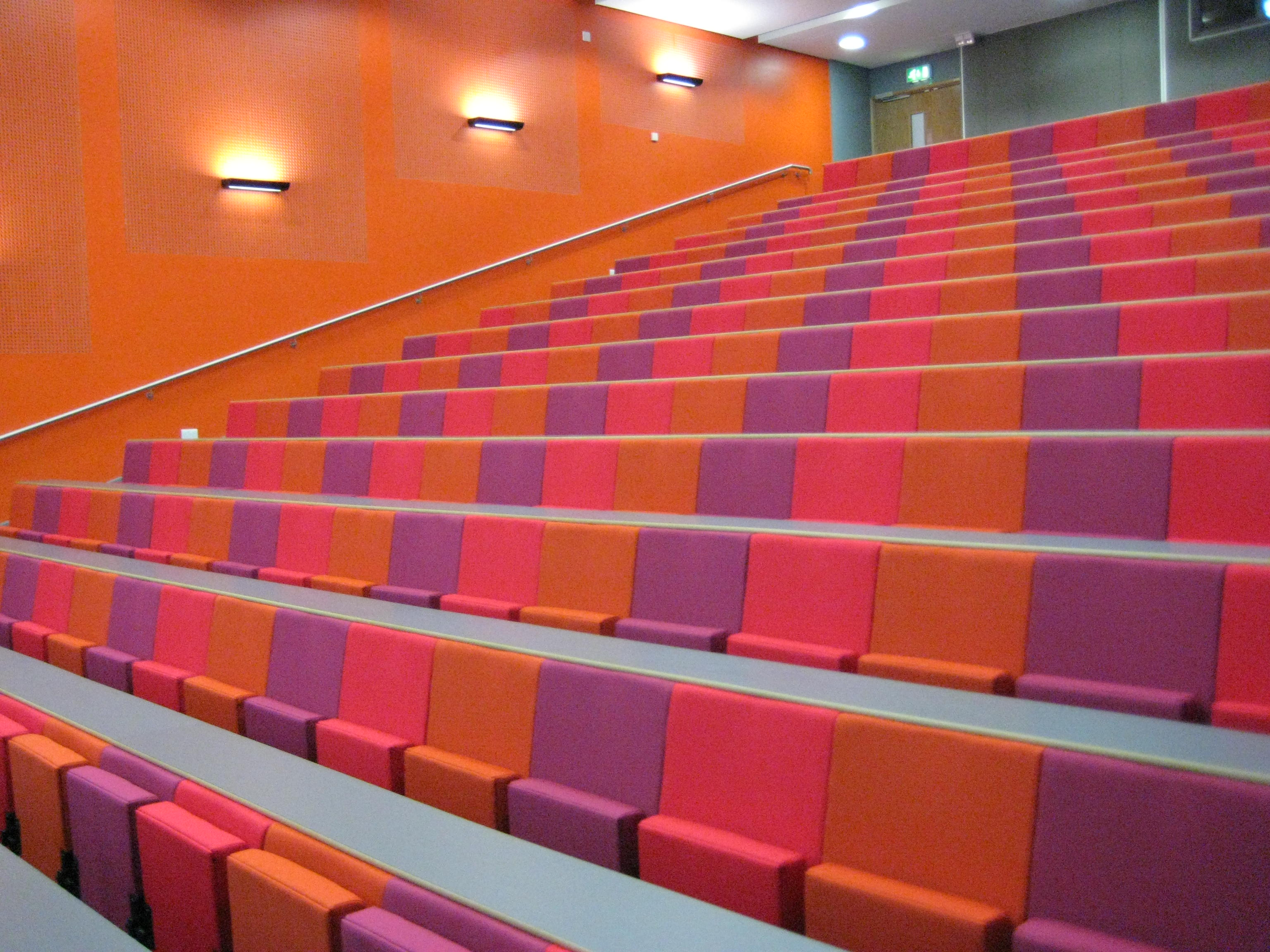 Rows of pink, orange and purple lecture chairs in a large university lecture theatre