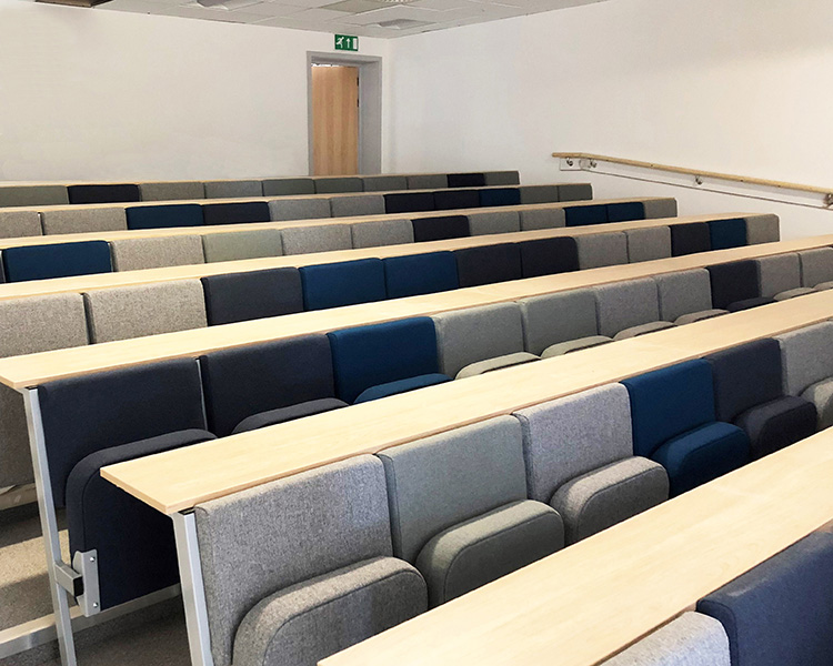 Rows of grey and blue lecture chairs in a university lecture room